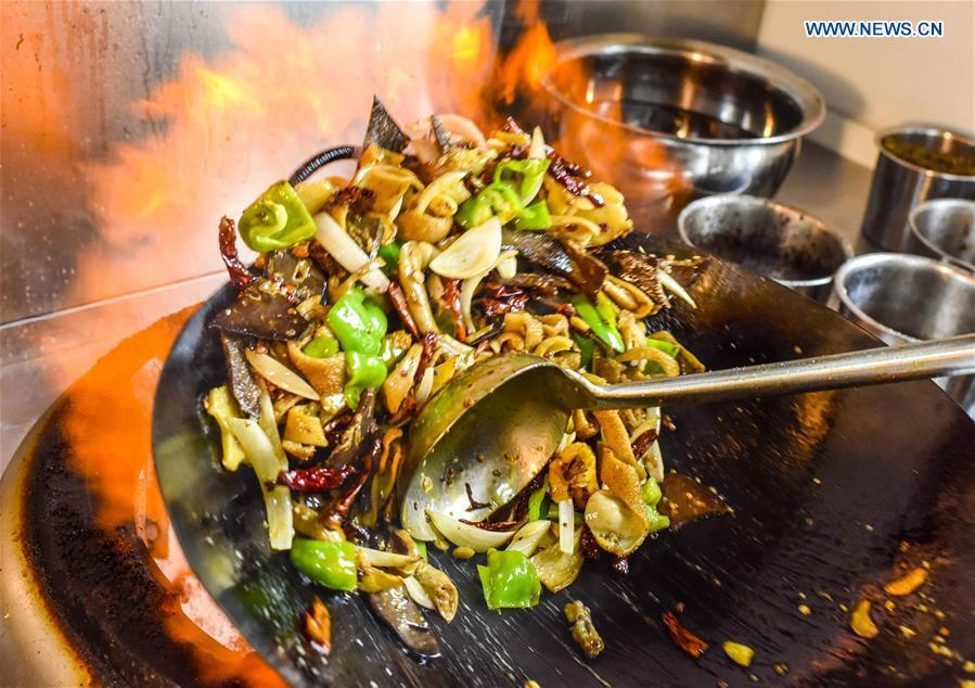 A cook makes a dish at a restaurant in Qitai County, northwest China\'s Xinjiang Uygur Autonomous Region, July 25, 2018. (Xinhua/Zhao Ge)