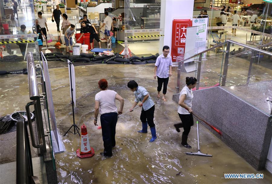 Staff of a shop drain the floodwater in Haikou, south China\'s Hainan Province, Aug. 10, 2018. Hainan was hit by heavy rainfalls under the influence of a tropical depression on Friday, which triggered a red alert for rainstorms in seven cities and counties, including Haikou. (Xinhua/Wang Junfeng)