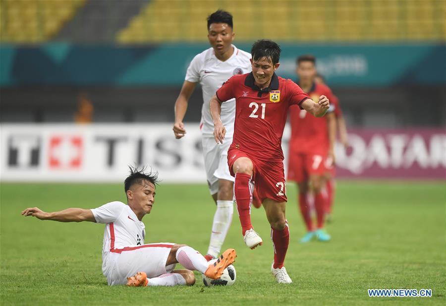 Yu Pui Hong (L) of Hong Kong of China vies with Bounmalay Tiny of Laos during the Men\'s Football Group A match between Hong Kong of China and Laos at the 18th Asian Games at Patriot Stadium in Bekasi, Indonesia, Aug. 10, 2018. (Xinhua/Jia Yuchen)
