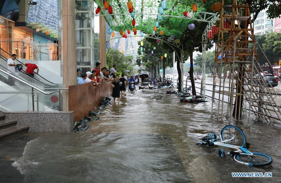 Bikes are swept down by the flood in Haikou, south China\'s Hainan Province, Aug. 10, 2018. Hainan was hit by heavy rainfalls under the influence of a tropical depression on Friday, which triggered a red alert for rainstorms in seven cities and counties, including Haikou. (Xinhua/Wang Junfeng)