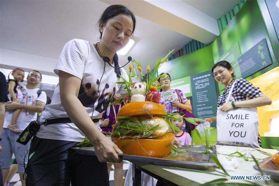 A staff worker shows a birthday cake prepared for the giant panda twins Hehe and Jiujiu at the Nanjing Hongshan Forest Zoo in Nanjing, capital of east China\'s Jiangsu Province, Aug. 10, 2018. Staff workers at the zoo celebrated the 3rd birthday anniversary for the female giant panda twins \