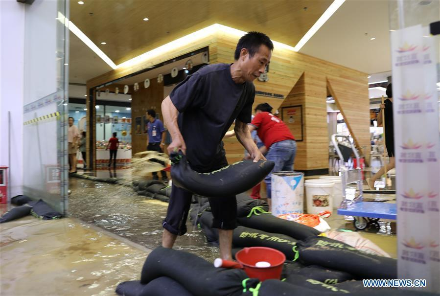 A staff of a shop carries a sand bag to keep away flood water in Haikou, south China\'s Hainan Province, Aug. 10, 2018. Hainan was hit by heavy rainfalls under the influence of a tropical depression on Friday, which triggered a red alert for rainstorms in seven cities and counties, including Haikou. (Xinhua/Wang Junfeng)