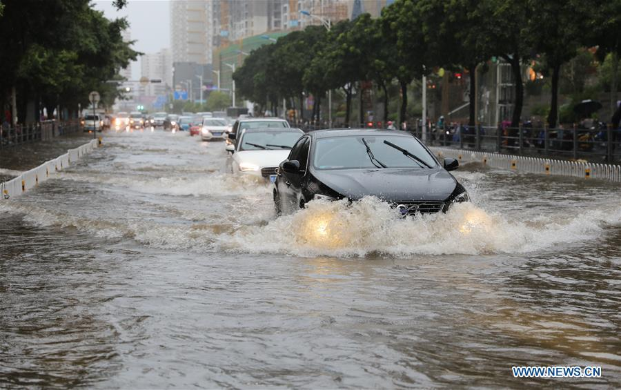 Cars run through the floodwater in Haikou, south China\'s Hainan Province, Aug. 10, 2018. Hainan was hit by heavy rainfalls under the influence of a tropical depression on Friday, which triggered a red alert for rainstorms in seven cities and counties, including Haikou. (Xinhua/Wang Junfeng)