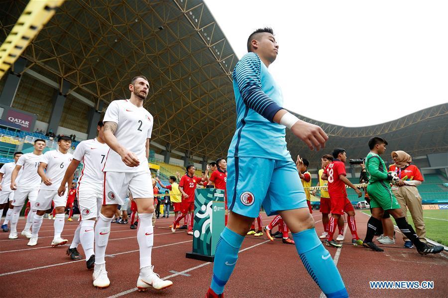 Players of Hong Kong of China and Laos enter the field before the Men\'s Football Group A match between Hong Kong of China and Laos at the 18th Asian Games at Patriot Stadium in Bekasi, Indonesia, Aug. 10, 2018. Hong Kong of China won 3-1. (Xinhua/Wang Lili)