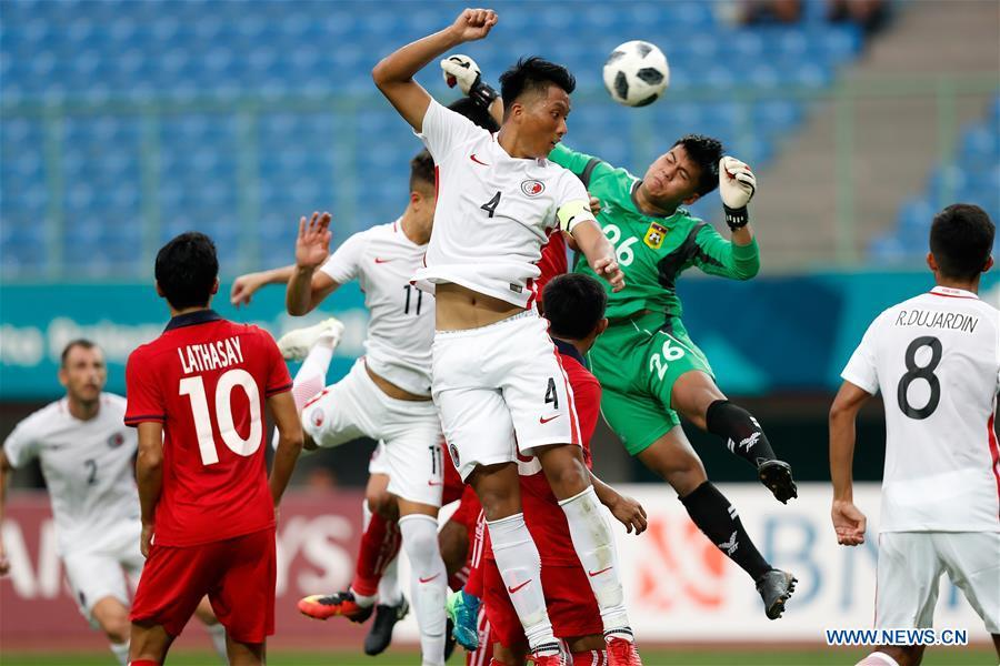 Lau Hok Ming (C) of Hong Kong of China vies with Paseuth Saymanolynh (2nd R) of Laos during the Men\'s Football Group A match at the 18th Asian Games at Patriot Stadium in Bekasi, Indonesia, Aug. 10, 2018. Hong Kong of China won 3-1. (Xinhua/Wang Lili)