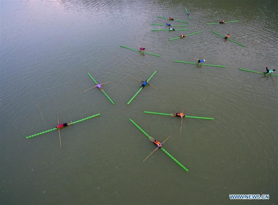 Middle school students practice single bamboo drifting on water in Rongjiang County, southwest China\'s Guizhou Province, Aug. 11, 2018. Single bamboo drifting originated in China\'s Guizhou and requires a person to stand or sit on a single piece of bamboo while performing graceful movements. (Xinhua/Wang Bingzhen)