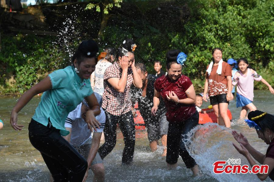 People from the Miao ethnic group catch fish barehanded or with tools during a folk festival at a river in Taijiang County, Southwest China\'s Guizhou Province, Aug. 12, 2018. The fishing festival, held on July 2 of the lunar calendar, which falls on Aug. 12 this year, is a chance for recreation and bonding among locals. (Photo: China News Service/Liu Kaifu)