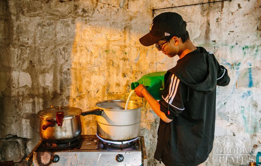 A man prepares to boil the fresh yak milk by pouring it into a pot. (Photo: Li Hao/GT)