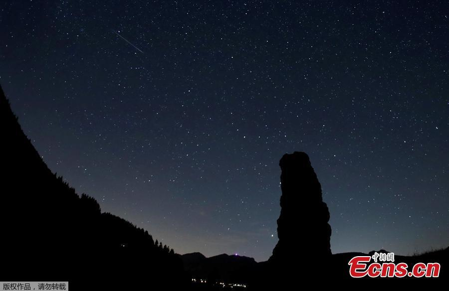 A meteor streaks past stars in the night sky next to the Cornieule of Tomeley standing stone during the annual Perseid meteor shower in La Forclaz, Switzerland August 11, 2018. (Photo/Agencies)