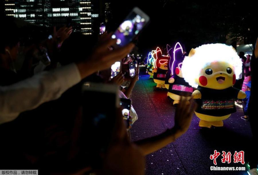 People take picture of performer swearing Pokemon\'s character Pikachu costumes during a night parade in Yokohama, Japan August 10, 2018.  A total of over 1,500 Pikachus (in both frolicking and decorative forms) will be greeting visitors to Yokohama's Minato Mirai harbor district. (Photo/Agencies)