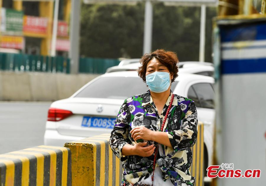 A woman wears a mask to protect her from a sandstorm while walking on a street in Urumqi, capital of Northwest China's Xinjiang Uygur Autonomous Region, Aug. 12, 2018. Visibility was reduced as dust shrouded the city, where temperatures reached approximately 35 degrees centigrade. (Photo: China News Service/Liu Xin)
