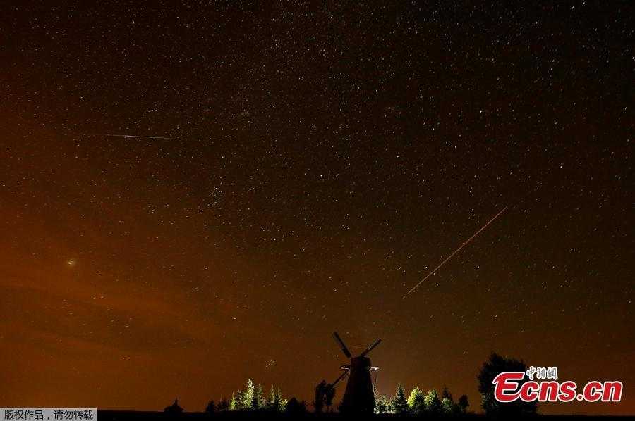 A meteor (L) and plane (R) tracks are seen in the night sky during the Perseid meteor shower near the village of Ptich, Belarus, August 13, 2018. (Photo/Agencies)