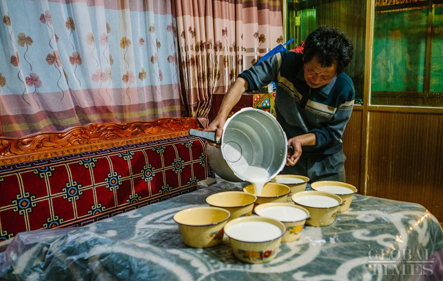The boiled milk is transferred to several small bowls to help it cool down.  (Photo: Li Hao/GT)