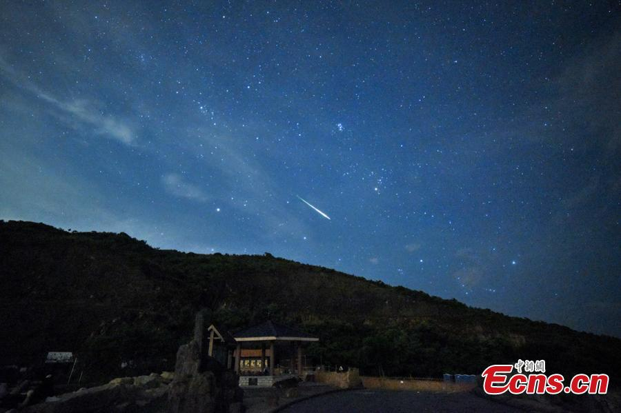 A meteor streaks past stars in the night sky during the Perseid meteor shower in Hong Kong, August 13, 2018. (Photo: China News Service/ Sheung Man Mak)