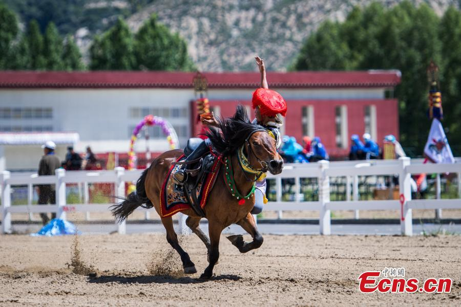 An equestrian puts on a display of traditional horsemanship skills during the Shoton Festival, commonly known as the Yogurt Festival, in Lhasa, Southwest China's Tibet Autonomous Region, Aug. 13, 2018. Equestrians performed ten kinds of stunts while riding a horse, including archery and toasting. (Photo: China News Service/He Penglei)