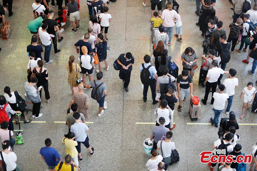 Passengers wait to change or refund tickets at a railway station in Shanghai, Aug. 13, 2018, after several trains were canceled due to Typhoon Yagi. Emergency rescuers are bracing for this year\'s 14th typhoon in the metropolis. (Photo: China News Service/Yin Liqin)