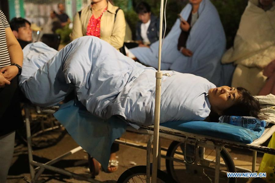 An injured person is transferred to safety area in Tonghai County, southwest China\'s Yunnan Province, Aug. 13, 2018. Eighteen people were injured after a magnitude-5 earthquake jolted Yunnan Province Monday morning, local authorities have said. The quake affected more than 48,000 residents in the counties of Tonghai and Huaning and the district of Jiangchuan, all administered by the city of Yuxi, damaging over 6,000 homes, according to a statement from the provincial civil affairs department. (Xinhua/Wang Anhaowei)
