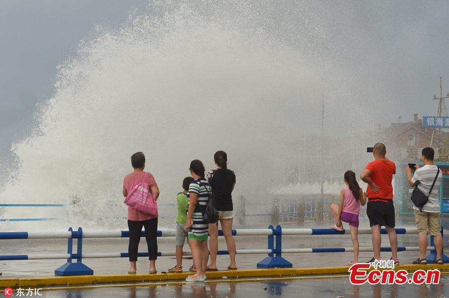 Visitors watch as huge waves, caused by Typhoon Yagi, pound the beach in Qingdao City, East China's Shandong Province, Aug. 14, 2018. (Photo/IC)