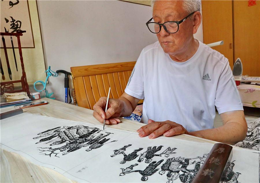 Wang Jingtang showcases his painting at his home in Qinhuangdao, North China\'s Hebei Province, on Aug. 10, 2018.