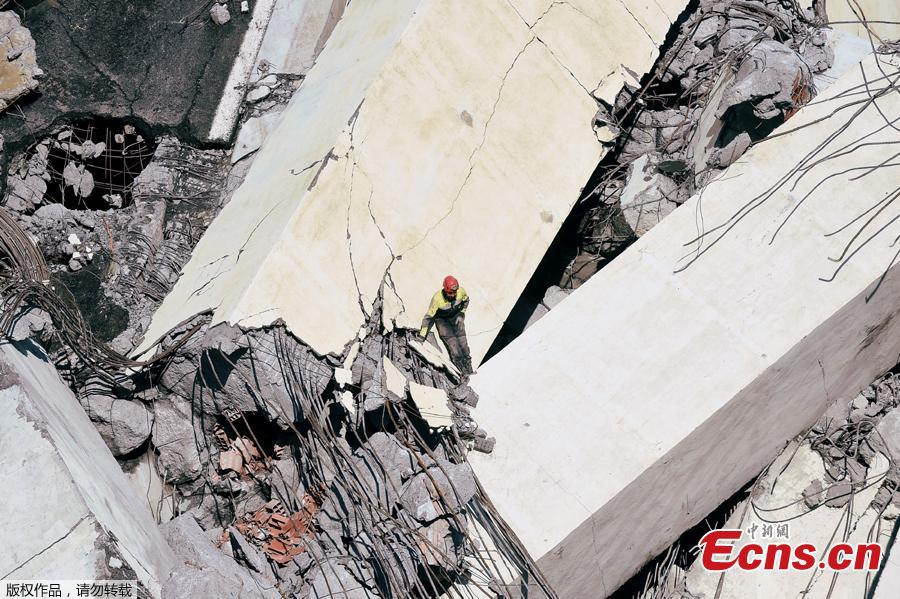 Rescue workers search on the site of the collapsed Morandi Bridge in the port city of Genoa, Italy August 14, 2018.The bridge connects the highway A10 to the western part of the city, near a populous neighborhood called Sampierdarena. At least 26 people were killed in the accident. (Photo/Agencies)