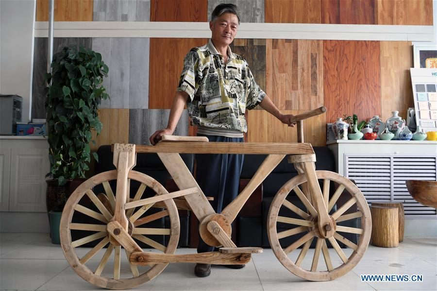 He Yong shows his wooden bicycle in Liuhu Township of Pingliang City, northwest China\'s Gansu Province, Aug. 14, 2018. The 55-year-old farmer He Yong successfully made a 1.8-meter-long and 0.98-meter-high wooden bicycle in 2017. The bike was made purely of wood, including walnut and elm. (Xinhua/Fan Peishen)