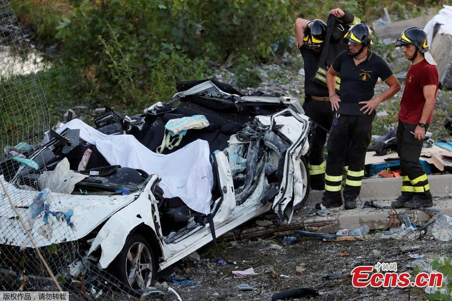 Firefighters stand next to a crushed car at the collapsed Morandi Bridge site in the port city of Genoa, Italy August 14, 2018. The bridge connects the highway A10 to the western part of the city, near a populous neighborhood called Sampierdarena. At least 26 people were killed in the accident.  (Photo/Agencies)