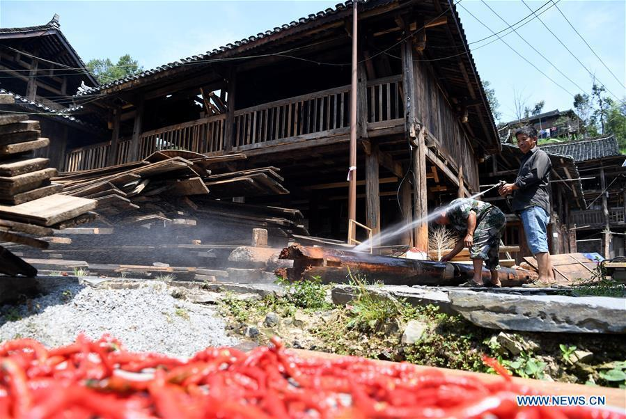 Villagers clean wood at an old wooden house in reform in Zaidang, Qiandongnan of southwest China\'s Guizhou Province, Aug. 14, 2018. Zaidang, a village of Dong ethnic group, has encouraged its villagers to make use of idle resources to upgrade local infrastructure, in an aim to develop tourism industry and shake off poverty. (Xinhua/Wang Bingzhen)