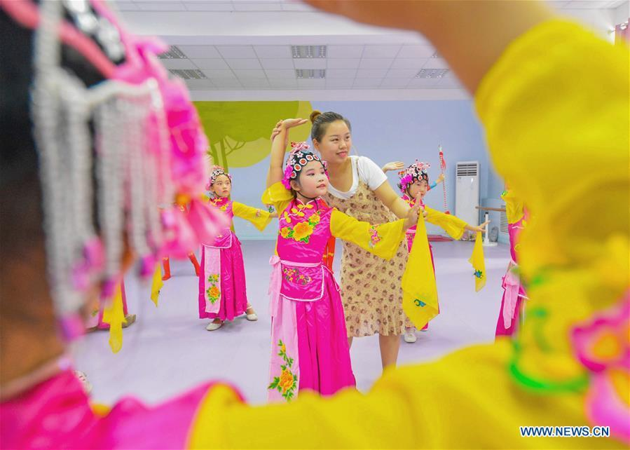 Students learn basic skills of traditional Chinese opera at a primary school in Hanshan District of Handan, north China\'s Hebei Province, Aug. 14, 2018. The school organized traditional Chinese arts activities for students to enrich their summer vacation life. (Xinhua/Wang Xiao)