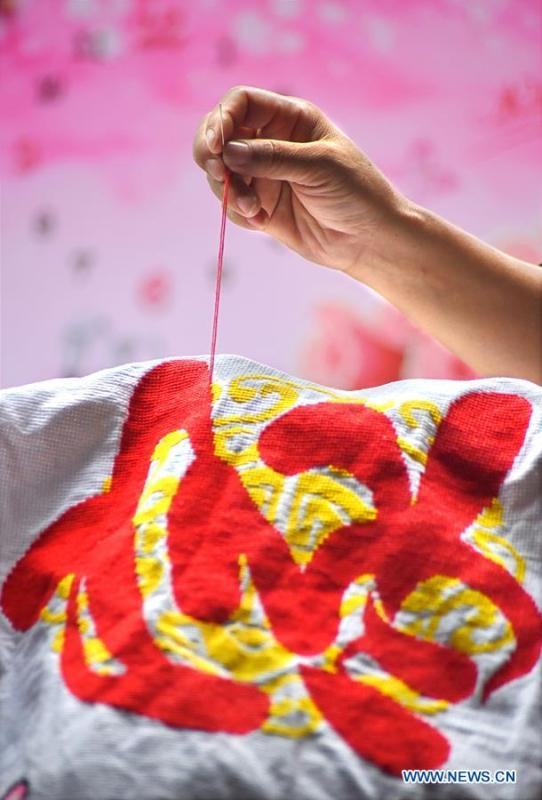 A woman makes a piece of embroidery in Yiyuan County of Zibo City, east China\'s Shandong Province, Aug. 14, 2018. In recent years, Yiyuan government has made efforts on the development of knitting and embroidery industry. Through establishing cooperatives and industry associations, the government helps to open up domestic and international market for products and raise income for the locals. (Xinhua/Zhao Dongshan)