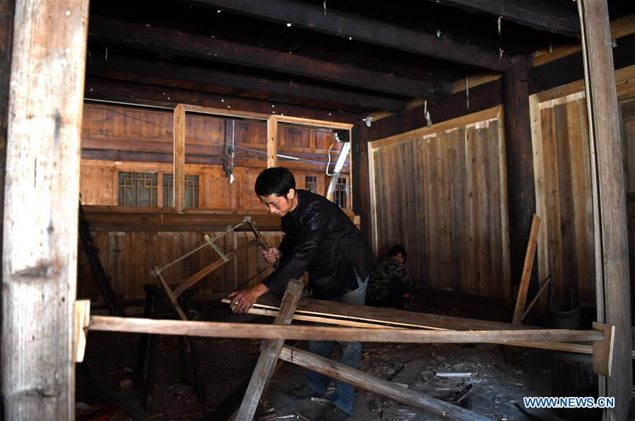A villager does carpenter work at an old wooden house in reform in Zaidang, Qiandongnan of southwest China\'s Guizhou Province, Aug. 14, 2018. Zaidang, a village of Dong ethnic group, has encouraged its villagers to make use of idle resources to upgrade local infrastructure, in an aim to develop tourism industry and shake off poverty. (Xinhua/Wang Bingzhen)