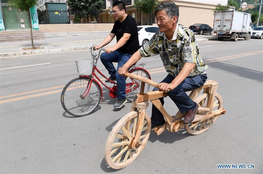 He Yong rides a wooden bicycle on a road in Pingliang City, northwest China\'s Gansu Province, Aug. 14, 2018. The 55-year-old farmer He Yong successfully made a 1.8-meter-long and 0.98-meter-high wooden bicycle in 2017. The bike was made purely of wood, including walnut and elm. (Xinhua/Fan Peishen)
