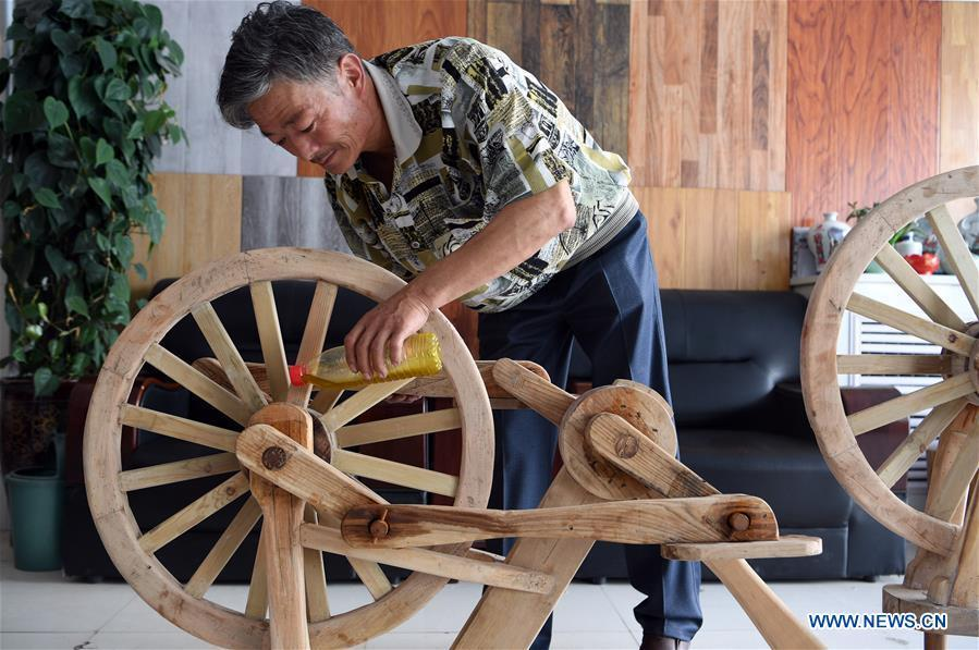 He Yong lubricates the bearing of a wooden bicycle in Liuhu Township of Pingliang City, northwest China\'s Gansu Province, Aug. 14, 2018. The 55-year-old farmer He Yong successfully made a 1.8-meter-long and 0.98-meter-high wooden bicycle in 2017. The bike was made purely of wood, including walnut and elm. (Xinhua/Fan Peishen)