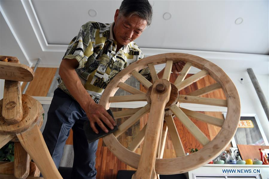He Yong polishes the wheel of a wooden bicycle in Liuhu Township of Pingliang City, northwest China\'s Gansu Province, Aug. 14, 2018. The 55-year-old farmer He Yong successfully made a 1.8-meter-long and 0.98-meter-high wooden bicycle in 2017. The bike was made purely of wood, including walnut and elm. (Xinhua/Fan Peishen)