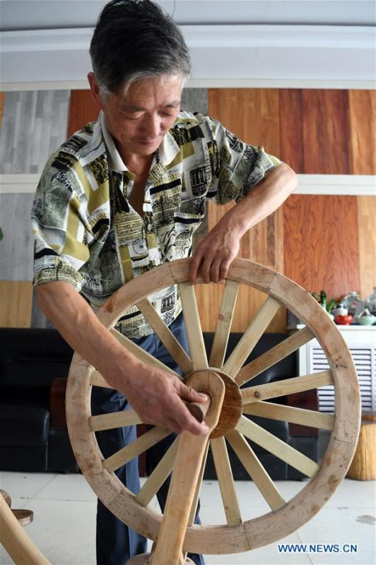 He Yong assembles the parts of a wooden bicycle in Liuhu Township of Pingliang City, northwest China\'s Gansu Province, Aug. 14, 2018. The 55-year-old farmer He Yong successfully made a 1.8-meter-long and 0.98-meter-high wooden bicycle in 2017. The bike was made purely of wood, including walnut and elm. (Xinhua/Fan Peishen)