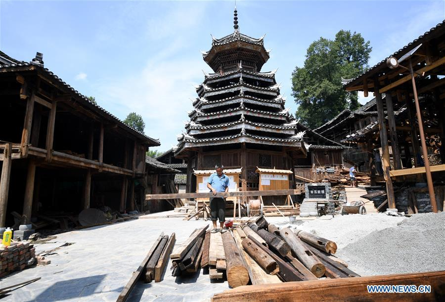 A villager carries wood at an old wooden house in reform in Zaidang, Qiandongnan of southwest China\'s Guizhou Province, Aug. 14, 2018. Zaidang, a village of Dong ethnic group, has encouraged its villagers to make use of idle resources to upgrade local infrastructure, in an aim to develop tourism industry and shake off poverty. (Xinhua/Wang Bingzhen)