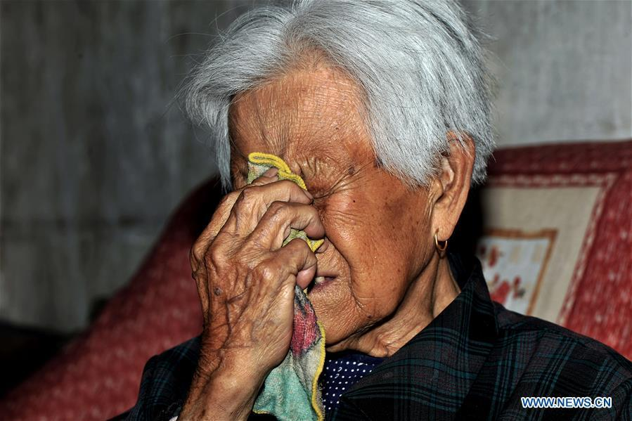 97-year-old Liu Gailian sheds tears as she speaks out her experiences as a \
