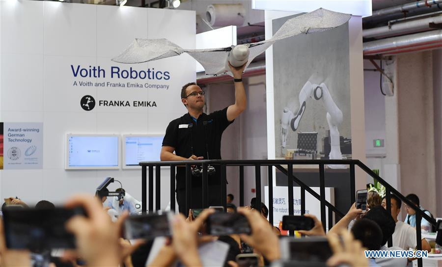 An exhibitor displays a bat-like bionic robot at World Robot Conference 2018 in Beijing, capital of China, Aug. 15, 2018. Kicking off on Wednesday, the Conference attracted contestants from 16 countries and regions to participate in the contest section. (Xinhua/Zhang Chenlin)