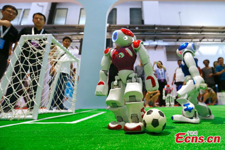 Robots play football at the World Robot Conference 2018 in Beijing, Aug. 15, 2018. The conference included a competitive section, which attracted contestants from 16 countries and regions. (Photo: China News Service/Fu Tian)