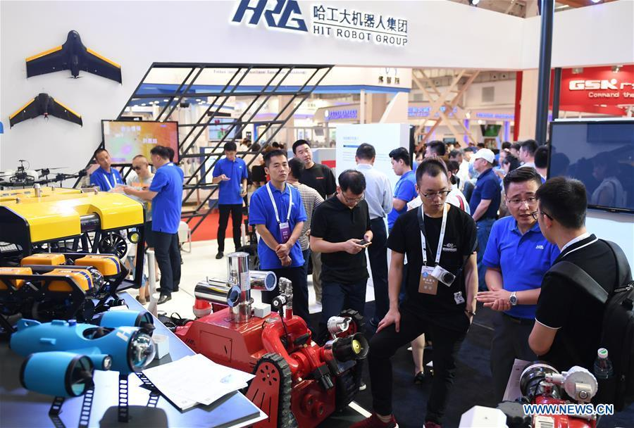 People visit the HIT Robot Group booth at World Robot Conference 2018 in Beijing, capital of China, Aug. 15, 2018. Kicking off on Wednesday, the Conference attracted contestants from 16 countries and regions to participate in the contest section. (Xinhua/Zhang Chenlin)