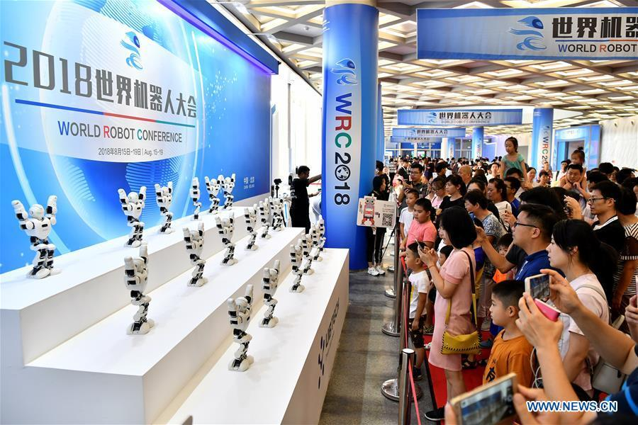 Visitors watch robots dancing performance at World Robot Conference 2018 in Beijing, capital of China, Aug. 15, 2018. Kicking off on Wednesday, the conference attracted more than 160 domestic and international corporations exhibiting their cutting-edge products in the robotics industry. (Xinhua/Li Xin)
