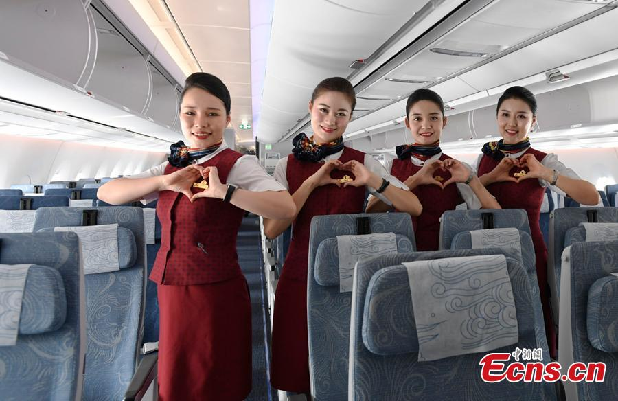 Stewardesses pose for a photo in Air China's first A350-900 aircraft, in Chengdu City, Sichuan Province, Aug. 15, 2018. Air China has configured the widebody aircraft with three classes, offering a total of 312 seats. The business class cabin has 32 seats laid out in a 1-2-1 reverse herringbone pattern. The premium economy cabin has 24 seats and the economy cabin offers 256 seats. (Photo: China News Service/An Yuan)