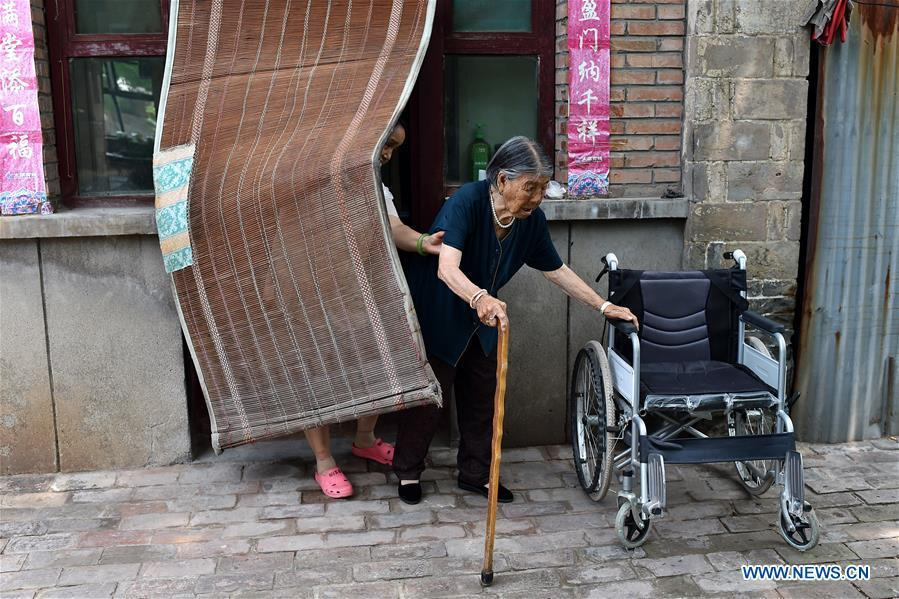 90-year-old Hao Yuelian (R) walks to a courtyard with the assistance of her daughter in Yanggongling Village of Wuxiang County, north China\'s Shanxi Province, July 24, 2018. In June of 1943, Hao was abducted by Japanese invaders. One month later, her family redeemed her from the Japanese army. After that, she was captured again and rescued by her father and brother. Women forced into sexual slavery by the Imperial Japanese Army before and during World War II were called \