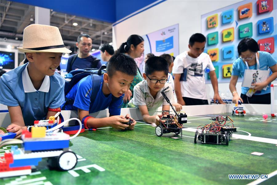 Children look at programming robots at World Robot Conference 2018 in Beijing, capital of China, Aug. 15, 2018. Kicking off on Wednesday, the conference attracted more than 160 domestic and international corporations exhibiting their cutting-edge products in the robotics industry. (Xinhua/Li Xin)