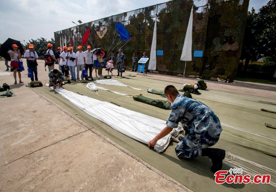 Soldiers arrange parachuting equipment during a military open day in Wuhan City, Central China's Hubei Province, Aug. 15, 2018. The event, supervised by the National Defense Education Office, attracted representatives of various military units as well as some 3,000 visitors. Since 2012, Wuhan has organized events allowing hundreds of thousands of people to visit barracks as part of national defense education. (Photo: China News Service/Zhang Chang)