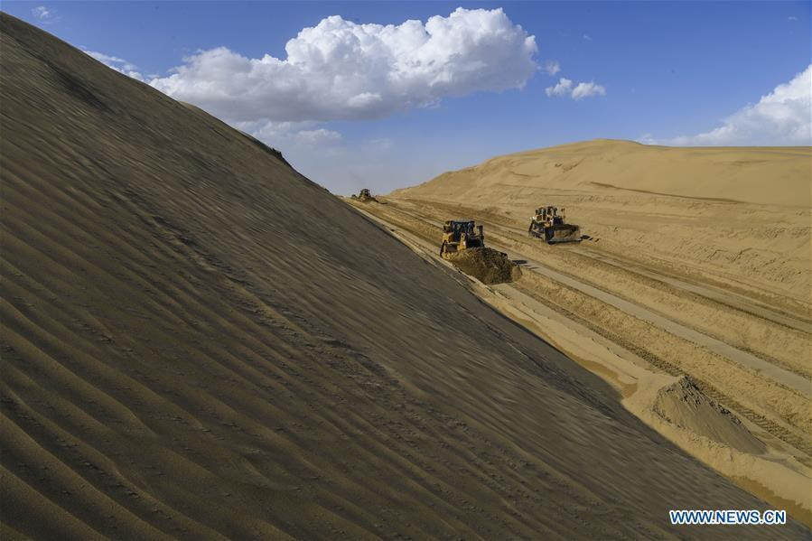 Vehicles work at a desert road construction site in Taklimakan desert in northwest China\'s Xinjiang Uygur Autonomous Region, July 5, 2018. An over 300-km-long desert road, linking Xinjiang\'s Yuli County to remote Qiemo County, is now under construction. It\'s the third that-kind-of road crossing China\'s largest desert Taklimakan nicknamed \