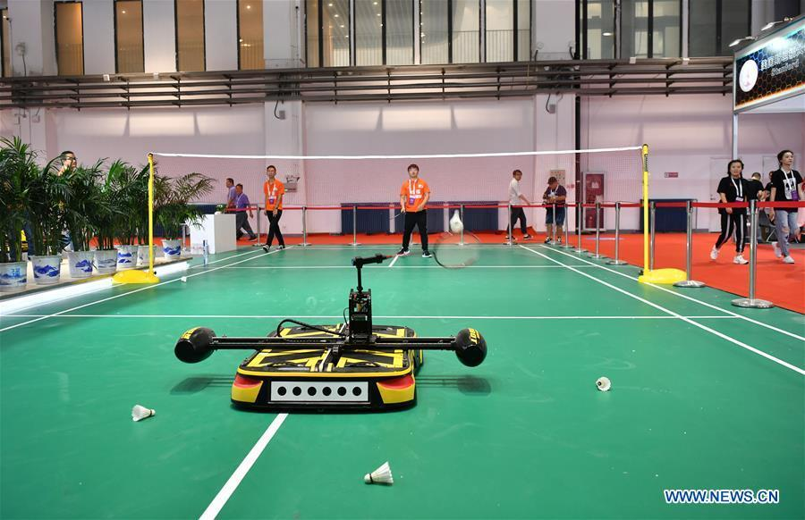 A robot plays badminton with an exhibitor at World Robot Conference 2018 in Beijing, capital of China, Aug. 15, 2018. Kicking off on Wednesday, the conference attracted more than 160 domestic and international corporations exhibiting their cutting-edge products in the robotics industry. (Xinhua/Li Xin)