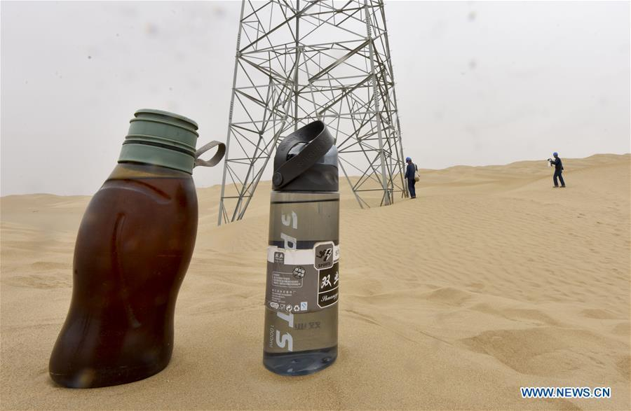 Photo taken on June 13, 2018 shows two bottles of water for linemen as they patrol along the Luntai-Tazhong-Qiemo-Ruoqiang power transmission and transformation line across the Taklimakan Desert in northwest China\'s Xinjiang Uygur Autonomous Region. The 563-kilometer power line across the Taklimakan Desert is the world\'s longest 220KV power transmission and transformation line. It was put into operation at the end of 2011, providing reliable power supply for local residents. The Taklimakan Desert, China\'s largest, is called \