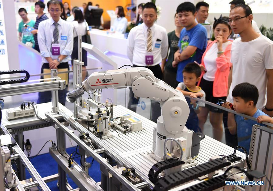 Visitors view an industrial robot at World Robot Conference 2018 in Beijing, capital of China, Aug. 15, 2018. Kicking off on Wednesday, the Conference attracted contestants from 16 countries and regions to participate in the contest section. (Xinhua/Zha