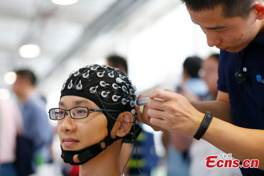 A visitor experiences a robot system at the World Robot Conference 2018 in Beijing, Aug. 15, 2018. The conference included a competitive section, which attracted contestants from 16 countries and regions. (Photo: China News Service/Fu Tian)