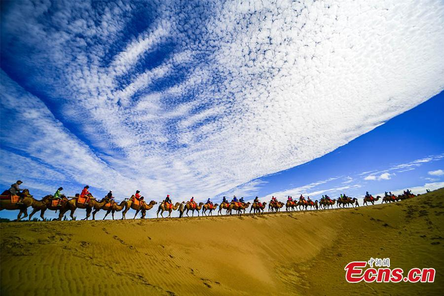 Tourists visit the Mingsha Hill scenic spot in the Gobi desert in Dunhuang City, Northwest China\'s Gansu Province, Aug. 15, 2018. Consisting of a group of sand dunes, the Mingsha Hill, or \